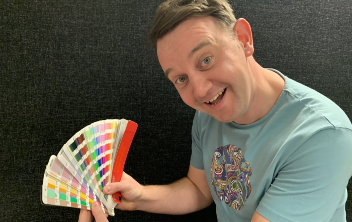 Graphic Designer Grainger holding pan-tone swatches